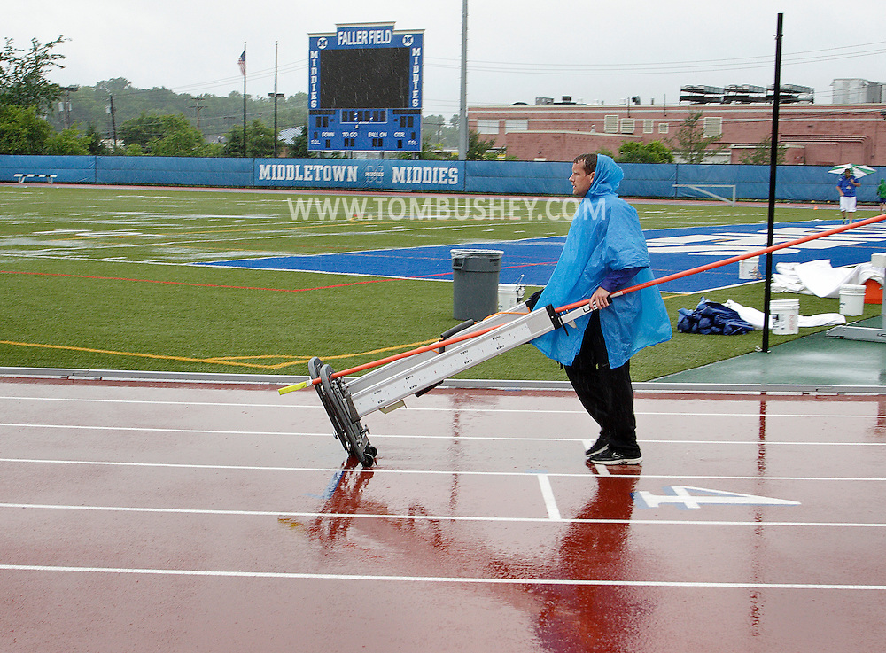 Middletown jumps coach Erik Rokeach wheels high jump standards away from the track at Middletown High School after the first day of the state track and field championships was postponed because of the wet weather on Friday, June 7, 2013.