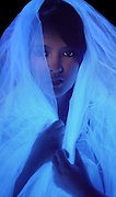 Portrait of a young girl with a glowing veil partially concealing her face.Black light