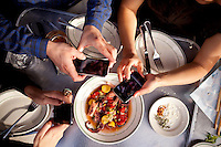 "(L-R) Soraya Darabi, 27, Ted Grubb, 30, and Alexa Andrzejewski, 27, take pictures with their mobile phones of the Octopus ""Bay of Naples Style"" appetizer at Delfina, in the Mission District, in San Francisco, Ca., on Wednesday, May 25, 2011. They are three entreprenuers who developed the iPhone app, Foodspotting."