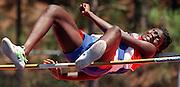 A high school athlete struggles to clear the high jump bar.
