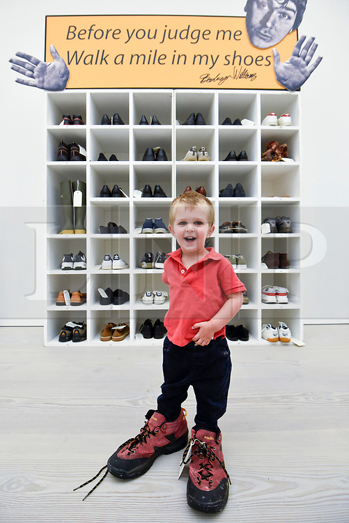 """© Licensed to London News Pictures. 27/09/2018. LONDON, UK. Emlyn Simmonds, aged two and a half, from Lewisham, wears a pair of size 13 shoes, in front of an installation called """"Walk A Mile In My Shoes"""", 2006, by Bedwyr Williams  Preview of """"Black Mirror"""", a major new exhibition featuring the work of 26 contemporary artists, at the Saatchi Gallery.  The show explores art's role in social satire and how political uncertainty has influenced art of recent years and runs 28 September to 13 January 2019.   Photo credit: Stephen Chung/LNP"""