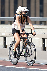 © Licensed to London News Pictures. 26/07/2018. London, UK. A cyclist wears a face mask to protect against high levels of pollution in London. Mayor of London Sadiq Khan has triggered a 'high' air pollution warning today. Today is predicted to be the hottest day of the year, with temperatures in the capital set to rise up to 35 degrees, as the UK experiences a prolonged heatwave. Photo credit : Tom Nicholson/LNP