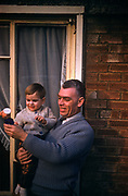 A 1960s father holds his young one year-old son, showing the child's favourite toy outside the family home, in March 1961, in Westcliff, Southend, Essex, England.