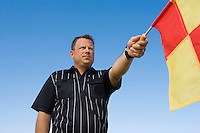 Soccer referee holding out penalty flag portrait