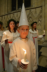 © Licensed to London News Pictures. 11/12/2015. York, UK. A member of the Vaxholm boys' choir from Stockholm prepares to join the procession during the Sankta Lucia Carol Service at York Minster. Lucia is a tradition in the Swedish calendar and is a celebration of St Lucy as the bringer of light in the darkness of winter.  Photo credit : Anna Gowthorpe/LNP