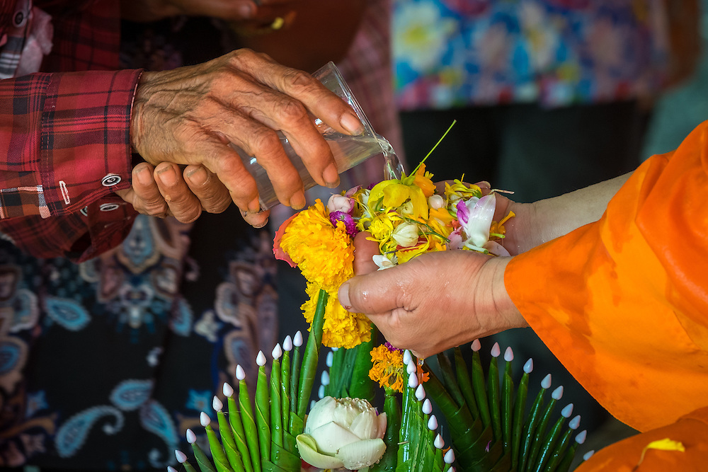 A devotee pours water over a monk's hands during a Songkran celebration in Rural Thailand 2016. PHOTO BY LEE CRAKER