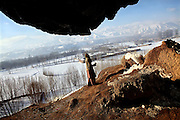 Fatemah, 12, is walking near the cave where she lives with her family since seven years, during a cold winter morning in Bamyan, central Afghanistan, an area mostly populated by Hazaras. A historically persecuted minority (15%) due to more lenient Islamic faith and characteristic 'Eastern' lineaments, Hazaras constitute the 70% of Bamyan's population.