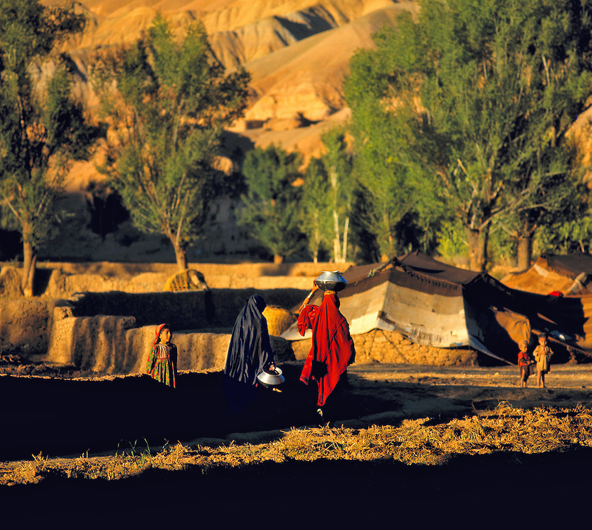 Women carry water for the evening meal in Bamian Valley, Afghanistan.