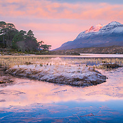 Brr! Looking at this image reminds me of arriving in the dark still half asleep, freezing morning with lots of hand rubbing and jumping up and down. No pain no gain though, gradually the first light appeared and the sky began to transform. The first rays glanced off Liathach and beautiful peaches and pinks bled through the clouds and saturated the icy reflection on Loch Clair. Warmed my soul