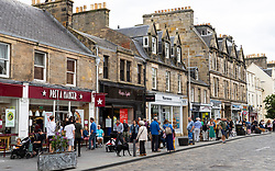 View of people and shops along busy Market Street in central St Andrews , Scotland, UK