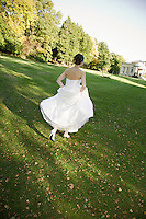 Mid-adult bride running in park