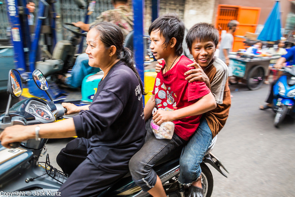 27 APRIL 2013 - BANGKOK, THAILAND:   A family rides a motorcycle in Talat Noi. The Talat Noi neighborhood in Bangkok started as a blacksmith's quarter. As cars and buses replaced horse and buggy, the blacksmiths became mechanics and now the area is lined with car mechanics' shops. It is one the last neighborhoods in Bangkok that still has some original shophouses and pre World War II architecture. It is also home to a  Teo Chew Chinese emigrant community.         PHOTO BY JACK KURTZ