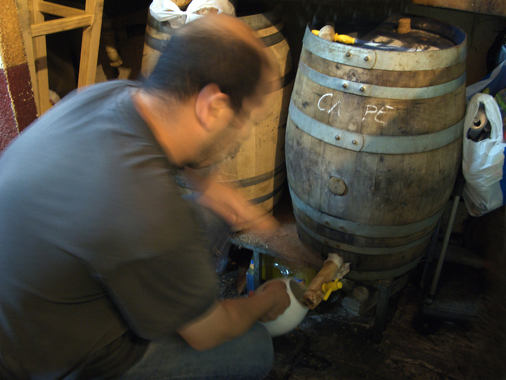 In a small bar in Santiago de Compostela, the local barman decants wine from a wooden barrel as has been done for hundreds of years. The wine was served in small bowls for EUR0.50 a bowl.