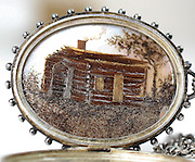 """Lock of Abraham Lincoln's Hair fashioned into the shape of a log cabin up for sale <br /> <br /> Unique pair of artistically fashioned locks of Abraham Lincoln's hair originating from a lock clipped by Dr. Charles Sabin Taft, who attended to the president on the night of his assassination. Most impressive is an ornately decorated oval locket, 2 x 1.5, which opens to reveal a superb rendering of the log cabin in Kentucky where Lincoln was born, accomplished using strands of his hair and set against a mother-of-pearl background. A handwritten notation displayed on the opposing side describes the piece, in full: """"Sketch of Abraham Lincoln's Birthplace, Harding, Ky, Feb. 12 1[80]9, Made from a lock of Lincoln's hair secured by Dr. Sabin Taft on the night of the assassination, April 14, 1865, Washington."""" A smaller brooch, 1 x .5, is decorated with jewels around the perimeter and displays a matching depiction of the cabin, also made using strands of this lock. A simple description is engraved on the reverse, in full: """"Lincoln. Apl. 14. 1865."""" In overall fine condition.<br /> <br /> Dr. Taft was a member of the audience watching Our American Cousin on the night of April 13, 1865, and was one of three doctors to attend to the president at the theatre after he was shot. Taft remained with Lincoln until his death the next day at the Petersen House and participated in the post-mortem examination, during which time he obtained a lock of the president's hair. These two wonderful presentations of this hair—fine pieces of folk art in their own right—were acquired directly from a Connecticut family descending from Abraham Pierson, a founder of Yale. The lock may have come into the family's possession via Julia Taft Bayne, the half-sister of Dr. Charles Sabin Taft, who married a congregational minister in Greenwich, Connecticut, in 1869; incidentally, Julia was a playmate of Willie and Tad Lincoln during the first two years of Lincoln's tenure in the White House, later writing a"""