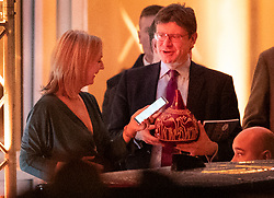 © Licensed to London News Pictures. 06/02/2019. London, UK. Chief Secretary to the Treasury Liz Truss (L) takes a phone photo of Business Secretary Greg Clark holding a raffle prize as they leave the Black and White Ball, a fundraiser held by the Conservative Party in Battersea Park. Photo credit: Peter Macdiarmid/LNP