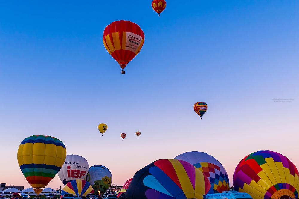 Hot air balloons lifting off at sunrise, Albuquerque International Balloon Fiesta, Albuquerque, New Mexico USA.