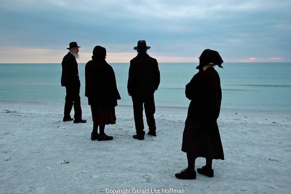 Amish at sunset on the beach at Long Boat Key, Florida.