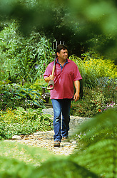 Alan Titchmarsh walking down the garden path with fork over his shoulder
