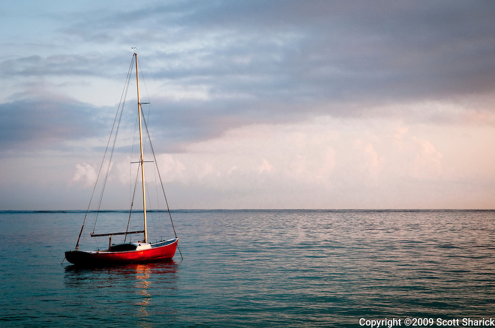 A sail boat at sunrise off Lanikai Beach in Hawaii.
