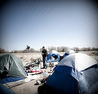 Marc Stevenson, standing, in a homeless encampment known as 'tent city'  on the banks of the American River in Sacramento, CA.