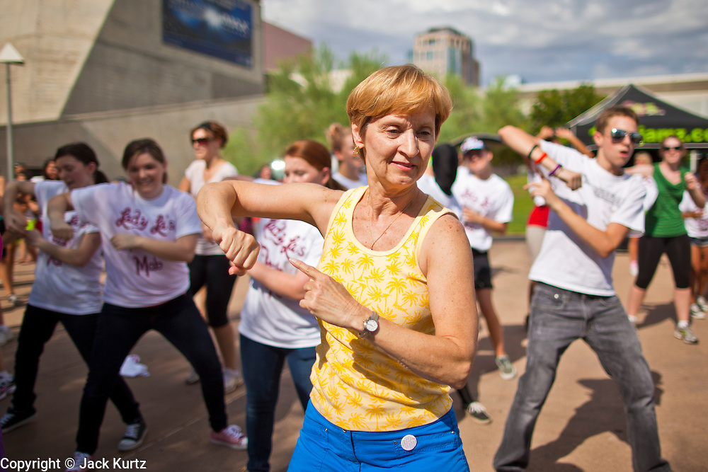 """30 JULY 2011 - PHOENIX, AZ:  REGINA PRYOR, from Tempe, AZ, dances as a part of a flash mob in Phoenix, AZ, Saturday. About 200 people showed up at Heritage Square in downtown Phoenix Saturday morning for a flash mob coordinated by the Arizona Science Center. The mob danced to several hip-hop songs before disbanding. The event was a part of National Dance Day Activities and the First Lady's """"Let's Move!"""" physical fitness campaign.    PHOTO BY JACK KURTZ"""