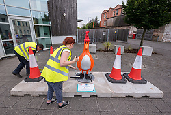 "© Licensed to London News Pictures.  01/07/2018; Bristol, UK. Gromit Unleashed 2. Staff put the finishing touches to the ""Oh Bollards"" Feathers McGraw character (disguised as a traffic cone), installed outside Aardman Animations at Bristol Harbourside for the Gromit Unleashed 2 sculpture trail. Gromit Unleashed 2 which officially begins on 02 July will see the Academy Award®-winning character Gromit by Nick Park at Aardman Animations returning to Bristol in 2018 for the second time on sculpture trails to raise money for  the Grand Appeal charity. The character of Gromit will be joined by Wallace and their arch nemesis Feathers McGraw. The trail will feature over 60 giant sculptures designed by high-profile artists, designers, innovators and local talent. Sculptures will be positioned in high footfall and iconic locations around Bristol and the surrounding area. Photo credit: Simon Chapman/LNP"