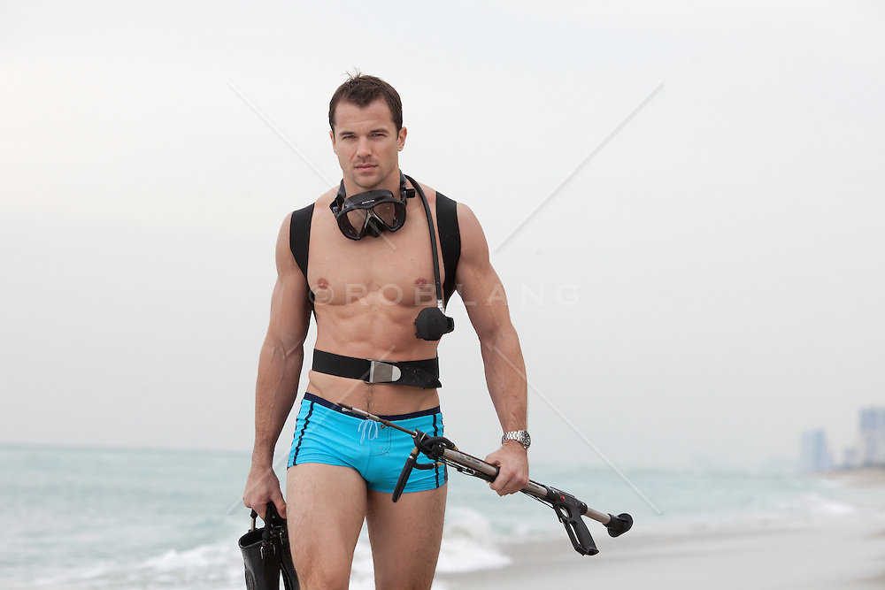 male snorkeler carrying a speargun and fines in the Atlantic Ocean in Florida