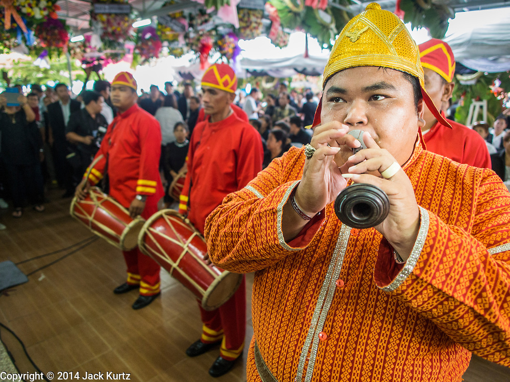 12 OCTOBER 2104 - BANG BUA THONG, NONTHABURI, THAILAND: Traditional Thai musicians perform at the first day of funeral rites for Apiwan Wiriyachai at Wat Bang Phai in Bang Bua Thong, a Bangkok suburb, Sunday. Apiwan was a prominent Red Shirt leader, member of the Pheu Thai Party of former Prime Minister Yingluck Shinawatra, and a member of the Thai parliament. The military government that deposed the elected government in May, 2014, charged Apiwan with Lese Majeste for allegedly insulting the Thai Monarchy. Rather than face the charges, Apiwan fled Thailand to the Philippines. He died of a lung infection in the Philippines on Oct. 6. The military government gave his family permission to bring him back to Thailand for the funeral. He will be cremated later in October. The first day of the funeral rites Sunday drew tens of thousands of Red Shirts and their supporters, in the first Red Shirt gathering since the coup.    PHOTO BY JACK KURTZ