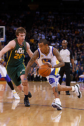 Feb 2, 2012; Oakland, CA, USA; Golden State Warriors shooting guard Monta Ellis (8) dribbles past Utah Jazz shooting guard Gordon Hayward (20) during the first quarter at Oracle Arena. Mandatory Credit: Jason O. Watson-US PRESSWIRE