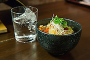 Tasmanian ocean trout and mushroom rice pot ready to serve. Beside the bowl is a glass of shochu, a distilled spirit, served on a large rock of ice.