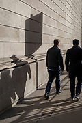 Business people walk down a pedestrian path between mainly insurance and financial businesses, in the City of London, the capital's financial district, on 28th January 2020, in the City of London.