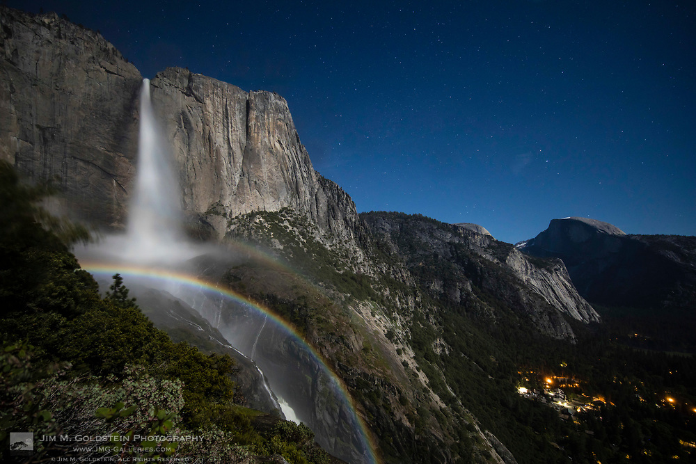 A wide arcing moonbow stretching across Upper Yosemite Falls on a clear night moonlit night in Yosemite National Park.