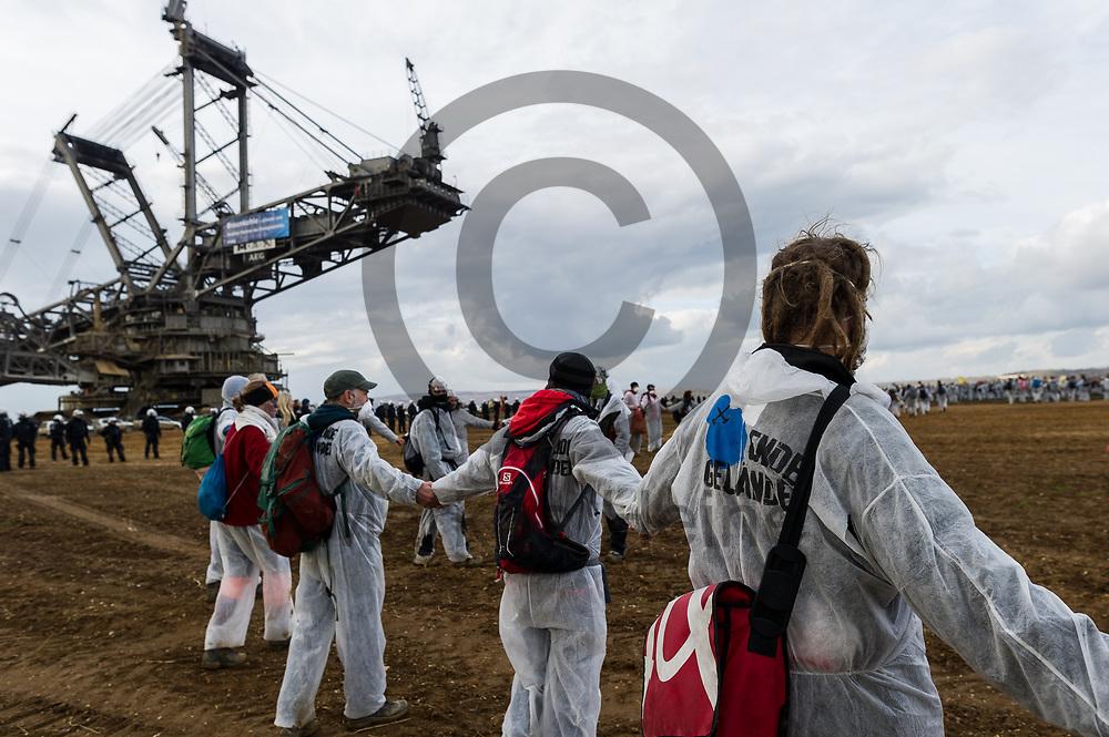 Deutschland, Elsdorf - 05.11.2017<br /> <br /> Aktivsten haben vor dem Bagger in der Grube einen Kreis gebildet. Circa 2500 Aktivisten drangen in die Grube des Braunkohle Tagebau Hambach ein um mit der Aktion f&uuml;r einen sofortigen Kohleausstieg zu protestieren. Die Aktion fand im Rahmen von Protesten im Vorfeld der UN-Klimakonferenz in Bonn statt.<br /> <br /> Germany, Elsdorf - 05.11.2017<br /> <br /> Activists have formed a circle in front of the excavator in the pit. Approximately 2500 activists invaded the pit of the lignite opencast mine Hambach to protest for an immediate coal exit. The action took place during protests prior to to the UN Climate Change Conference in Bonn.<br /> <br />  Foto: Markus Heine<br /> <br /> ------------------------------<br /> <br /> Ver&ouml;ffentlichung nur mit Fotografennennung, sowie gegen Honorar und Belegexemplar.<br /> <br /> Bankverbindung:<br /> IBAN: DE65660908000004437497<br /> BIC CODE: GENODE61BBB<br /> Badische Beamten Bank Karlsruhe<br /> <br /> USt-IdNr: DE291853306<br /> <br /> Please note:<br /> All rights reserved! Don't publish without copyright!<br /> <br /> Stand: 11.2017<br /> <br /> ------------------------------