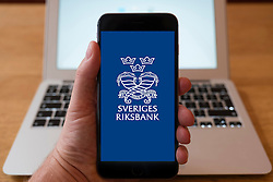 Using iPhone smart phone to display website logo of Sveriges Riksbank, Riksbanken, central bank of Sweden.