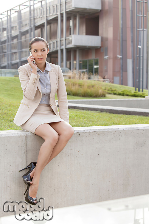 Full length of young businesswoman using mobile phone while sitting on wall against office building