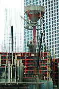 Israel, Tel Aviv, Man pouring concrete on a construction site at Azrieli Centre January 2008