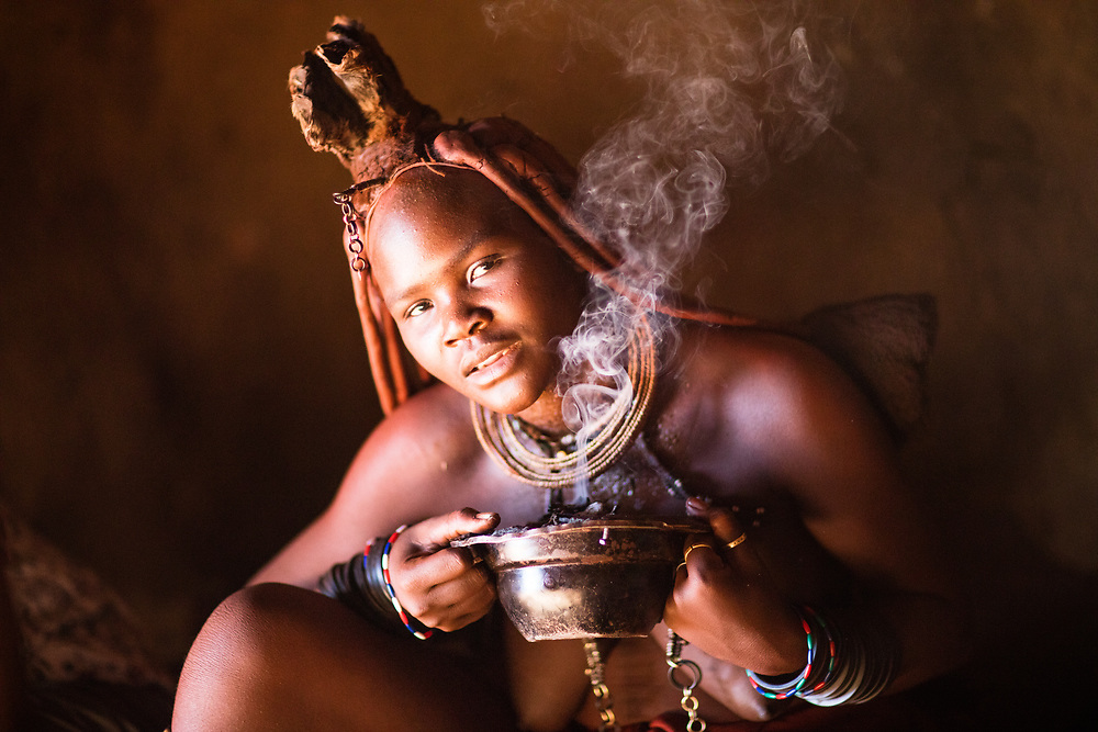 Himba girl perfuming self