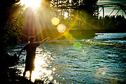 Young man fishing on Swan River near bridge in Bigfork