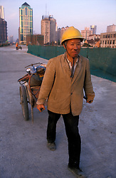 CHINA SHANGHAI PUDONG MAY99 - A Chinese construction worker pulls a trolley with equipment across the new highway flyover in downtown Shanghai. Pudong has experienced a dramatic rise in construction projects, although vacancy rates stand at nearly 60% and a bust-cycle is imminent.  ..jre/Photo by Jiri Rezac ..© Jiri Rezac 1999..Contact: +44 (0) 7050 110 417.Mobile:  +44 (0) 7801 337 683.Office:  +44 (0) 20 8968 9635..Email:   jiri@jirirezac.com.Web:     www.jirirezac.com..© All images Jiri Rezac 1999 - All rights reserved.