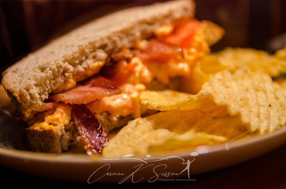 A Southern-style pimiento cheese sandwich is served on whole-grain bread, accented with bacon and fresh-sliced tomatoes, and served with potato chips. (Photo by Carmen K. Sisson/Cloudybright)
