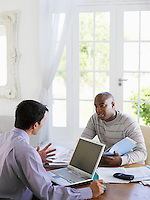 Man sitting at dinning table with financial advisor