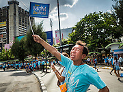 16 AUGUST 2015 - BANGKOK, THAILAND:  A man waves a ''Ride For Mom'' flag on Phayathai Road at Victory Monument during the ''Ride for Mom'' in Bangkok. More than 100,000 people across Thailand participated in the Bike For Mom event in honor of Queen Sirikit, who celebrated her 83rd birthday August 12. In Bangkok, the ride was led by His Royal Highness Crown Prince Maha Vajiralongkorn, the Crown Prince of Thailand and Sirikit's only son. Queen Sirikit, who is in poor health and living in a hospital, was unable to attend the bike ride.    PHOTO BY JACK KURTZ