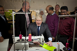 © Licensed to London News Pictures. 26/02/2013. London, UK. The Mayor of London, Boris Johnson, tries his hand at using a sewing machine at 'East End Manufacturing' in Bethnal Green, London today (26/02/2013). The mayor officially opened the East London clothing factory today and talked about his support for London based manufacturing. Photo credit: Matt Cetti-Roberts/LNP