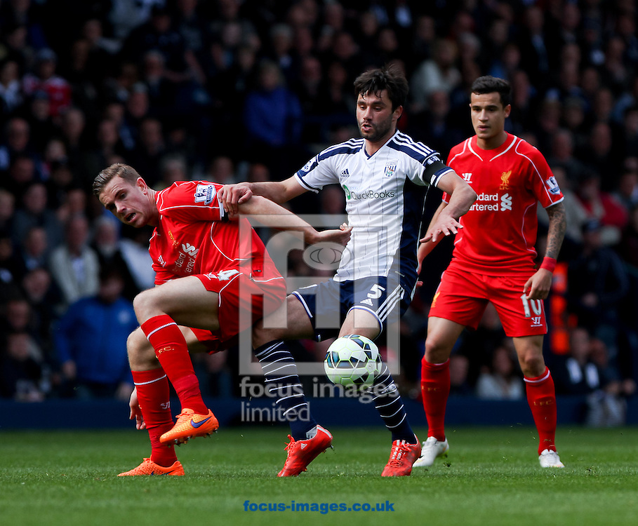 Claudio Yacob (centre) of West Bromwich Albion and Jordan Henderson (left) of Liverpool battle for the ball during the Barclays Premier League match at The Hawthorns, West Bromwich<br /> Picture by Tom Smith/Focus Images Ltd 07545141164<br /> 25/04/2015