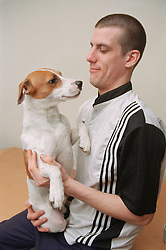 Resident of homeless hostel holding pet dog,