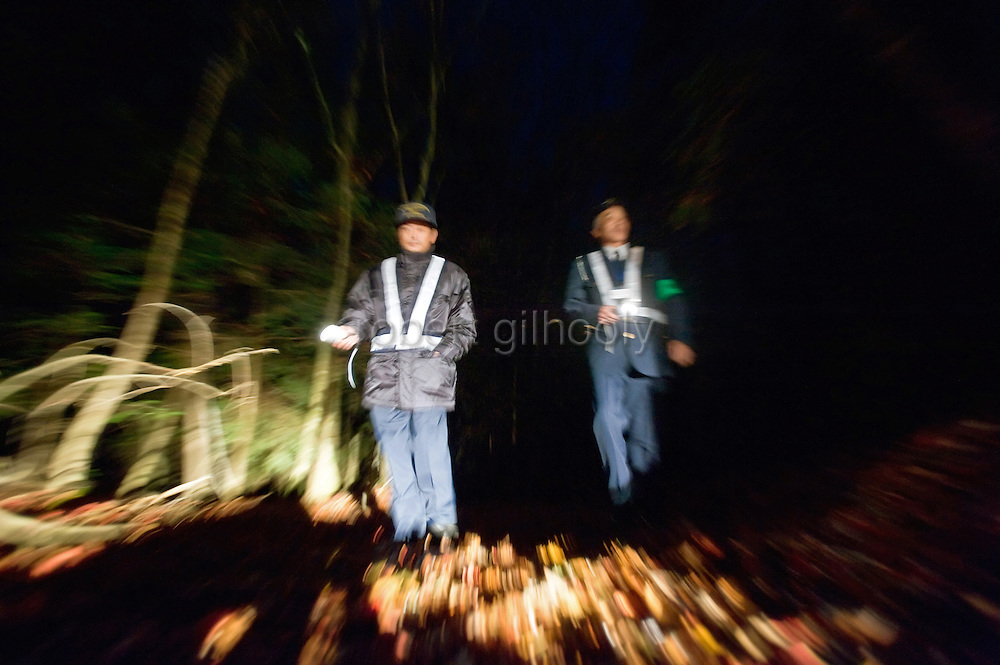 Yasuaki Komaya (L), and Yasunobu Fujie of the Yamanashi prefectural patrol association search for bodies or people contemplating suicide at Aokigahara Jukai in Yamanashi Prefecture, Japan on 02 Nov. 2009. The patrols and entranceway security cameras are among local initiatives to reduce the number of suicides in the forest.