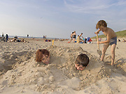 three boys at the beach having fun by being dug in