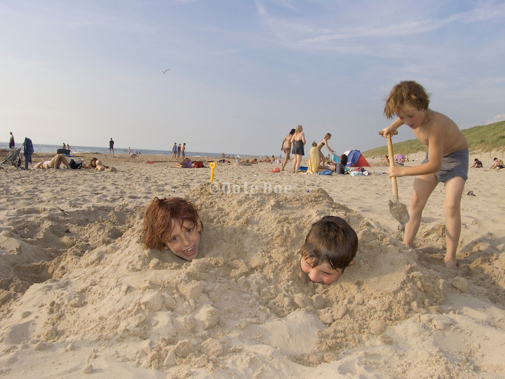 three boys at the beach having fun by being dug in