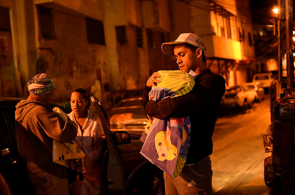 Yanaifre Acevedo's cousin and dance partner, Wleiker Salcedo, helps her out of the car and holds her baby, Dilan.  Salcedo said he never though Acevedo would be a teen mother, he said he thought she was more intelligent.