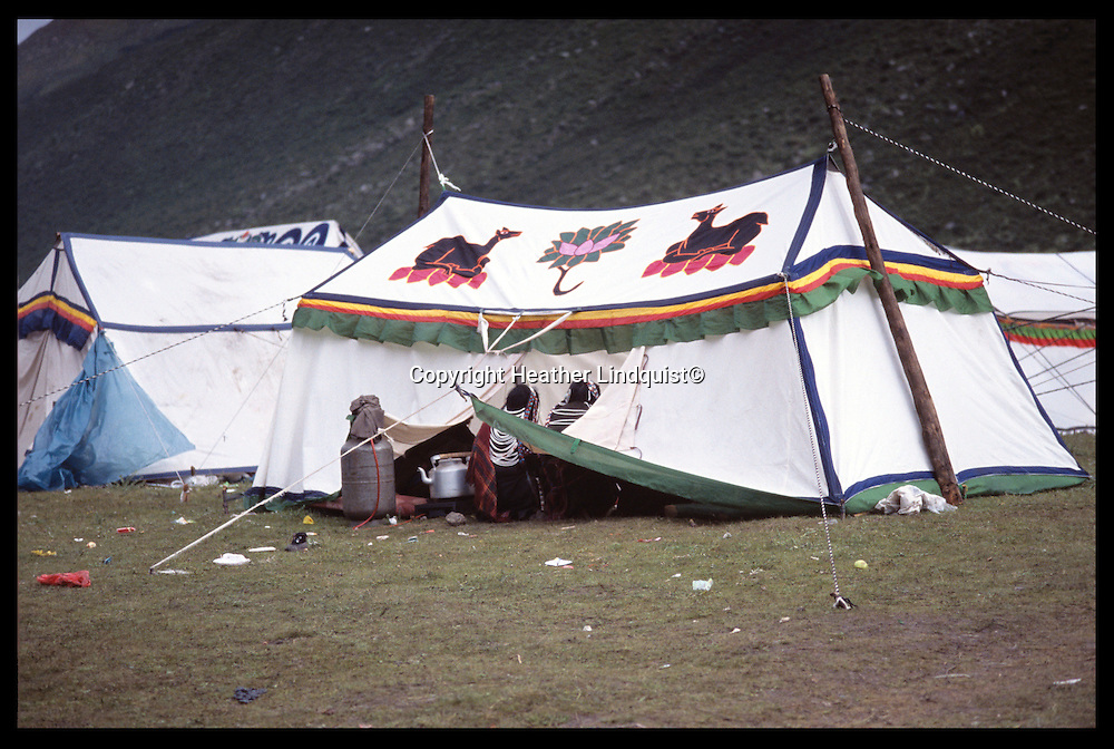 Two Tibetan women sit in the doorway of their tent.